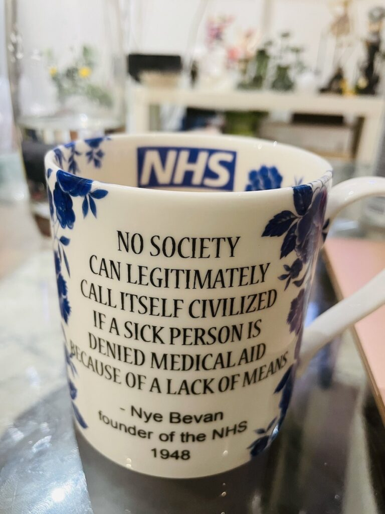 """NHS mug, with the NHS logo on its inside and this written on the outside: """"No society can legitimately call itself civilized if a sick person is denied medical aid because of a lack of means. — Nye Bevan, founder of the NHS, 1948"""""""""""